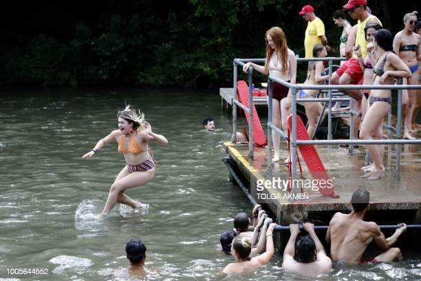 A bather leaps into the water at the mixedpond on Hampstead Heath in London on July 26 2018 Britain has been in the grip of its longest heatwave in...