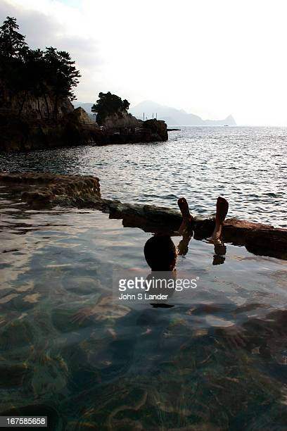 Bather looks out at the Pacific from an openair hot spring bath at Komatsu Hot Springs on the Izu Peninsula MODEL RELEASED