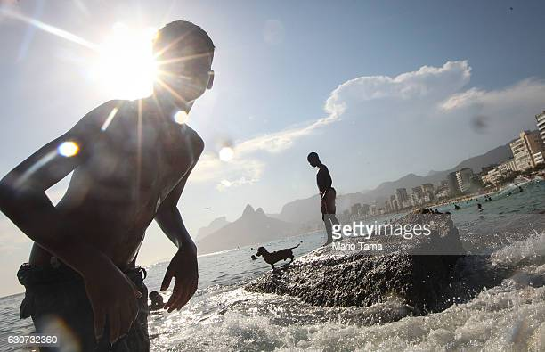 Bathers and a dog gather at Arpoador during New Year's Eve celebrations on December 31 2016 in Rio de Janeiro Brazil Fireworks will light the sky...