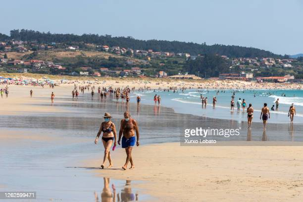 Bathers and tourists protect themselves from the Covid 19 pandemic, with the mask on their faces. This beach is one of the best known and longest in...