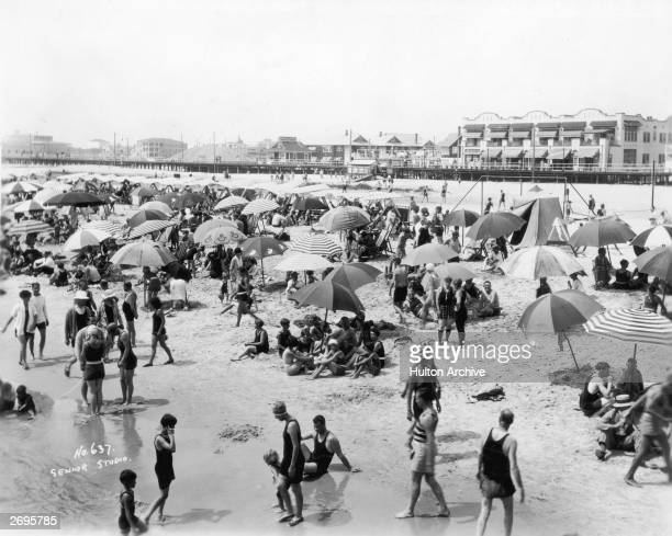 Bathers beach umbrellas and tents crowd the beach at Ocean City New Jersey The boardwalk is visible in the background