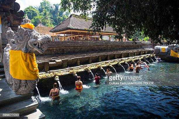 bathers in water at pura tirta empul temple, bali, indonesia - pura tirta empul temple stock pictures, royalty-free photos & images