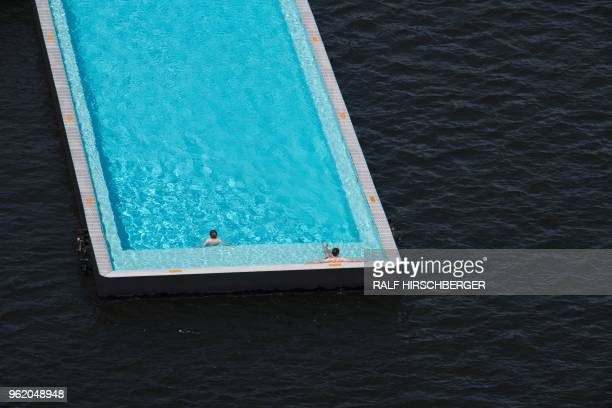Bathers relax in the Badeschiff a barge that functions as a floating swimming pool on the river Spree on May 24 2018 in Berlin where temperatures up...