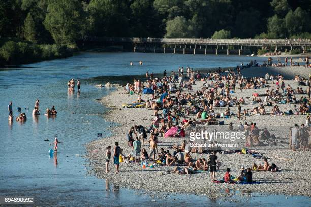 Bathers relax on the shore of the Isar river on June 11 2017 in Munich Germany Summer weather of blue skies and 29 degrees Celsius is drawing weekend...