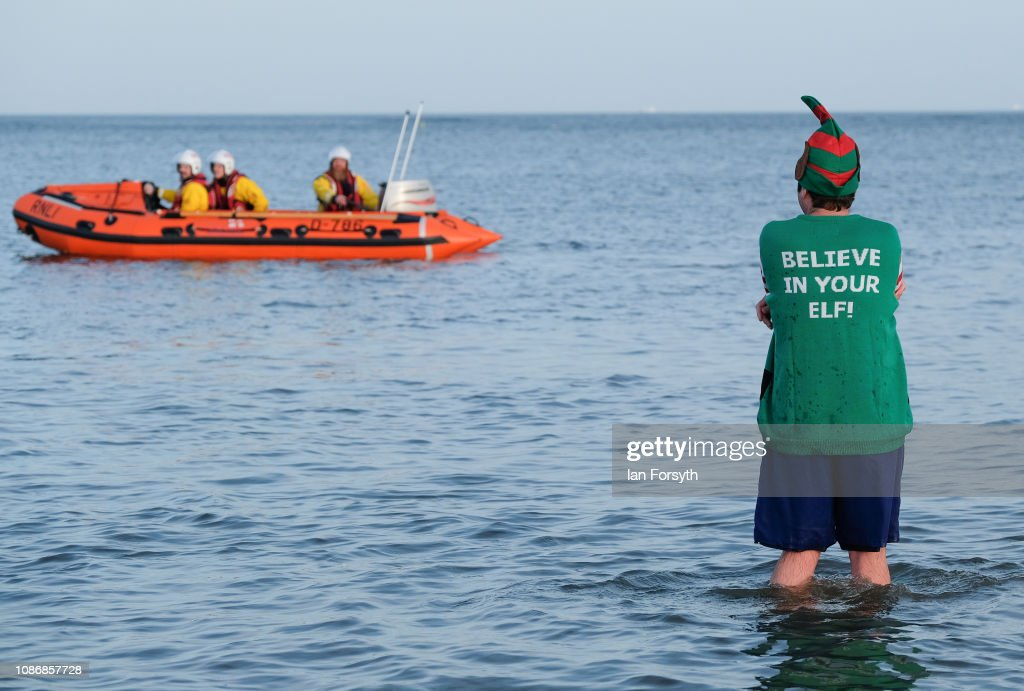 Bathers run into the cold waters of the North Sea as they take part