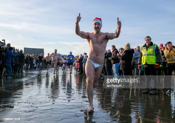 Bathers run into the cold waters of the North Sea as they take part in the annual Boxing Day dip on December 26 2018 in Redcar England The event...