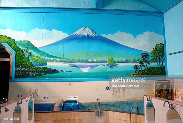 Bathhouse mural painting Upside Down Fuji by master Morio Nakajima is seen at Daikokuyu on October 21 2013 in Tokyo Japan Traditionally sento or...