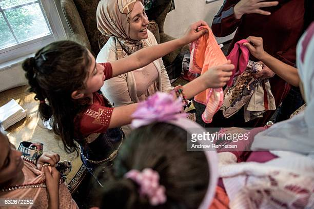 Bathing suits are given to children from the Syrian refugee community to go swimming during a community potluck on August 1 2015 in Bloomfield Hills...