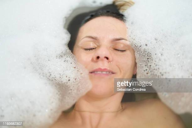 bathing woman relaxing in bath. - foam material stock pictures, royalty-free photos & images