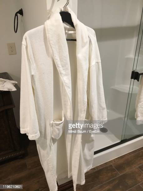 bathrobe hanging in coathanger at home - baum stock pictures, royalty-free photos & images
