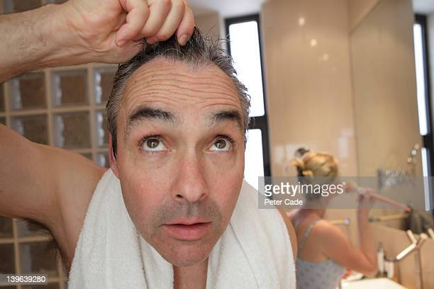 bathroom, man looking into camera/mirror - hair loss stock pictures, royalty-free photos & images