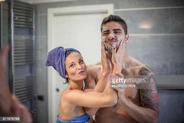 Bathroom mirror image of young woman applying shaving lotion to boyfriends cheeks