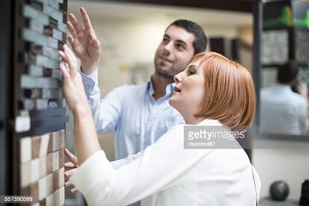 Bathroom shop salesman showing tile samples to female customer