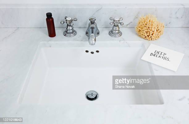 "bathroom sink next to a reminder note: deep breaths - ""shana novak"" stock pictures, royalty-free photos & images"