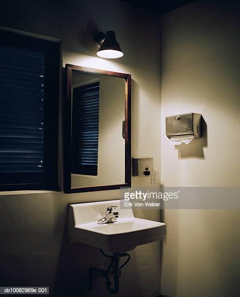Bathroom sink with light overhead, night