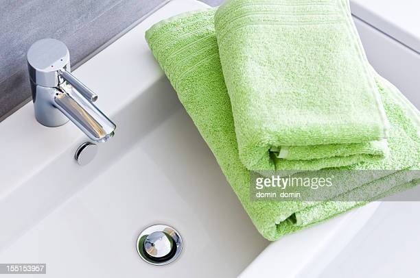 Bathroom sink with two clean green towels in different sizes