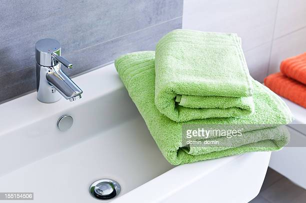 Bathroom sink with two green towels