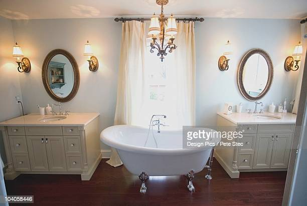 A Bathroom With Double Sinks And A Clawfoot Tub