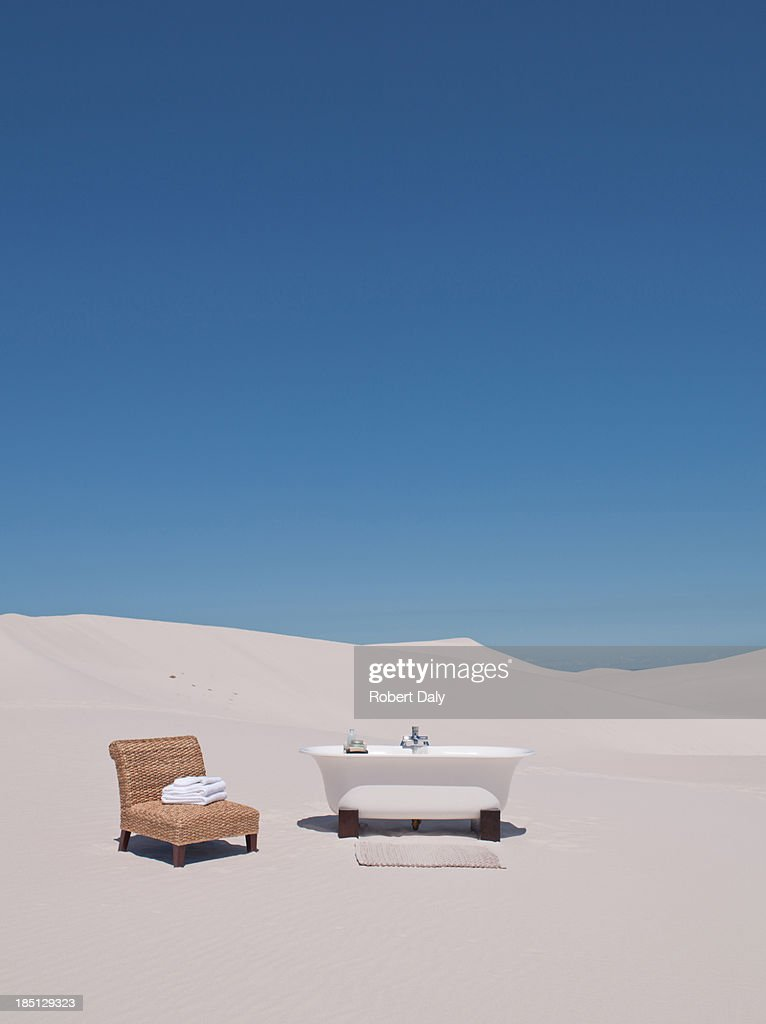 Bathtub and chair in desert : Stock Photo
