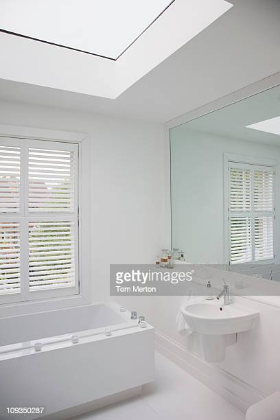 Bathtub and sink in modern, white bathroom