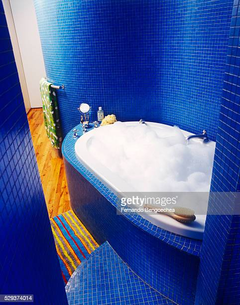 Bathtub filled with foam is seen in a playful bathroom with blue tiled walls