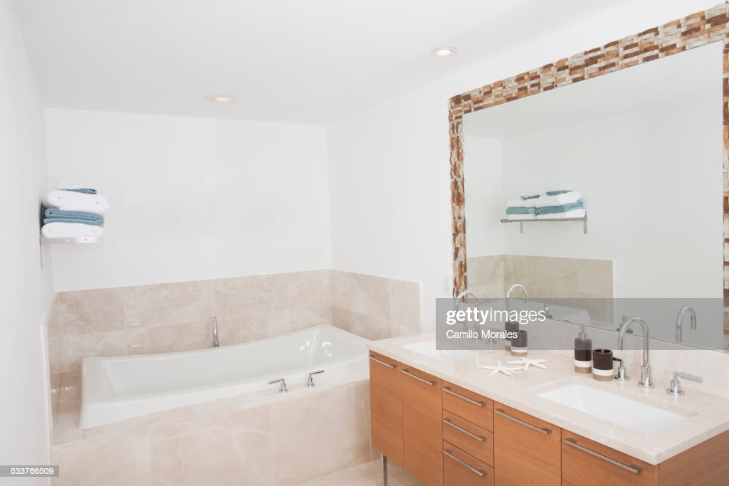 Bathtub, sinks and mirror in modern dining room : Foto stock