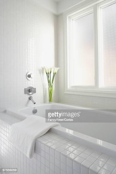 Bathtub with bath towel folded over edge