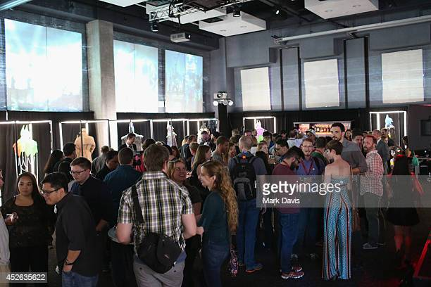 """Batman fans admire reimagined renditions of the hero's iconic cape and cowl during an unveiling of a """"Batman Arkham Knight"""" themed art exhibit during..."""