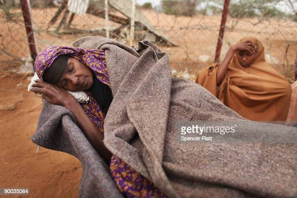 Batola Khalil Mohamed who is sick, rests in a wheelbarrow after making a three day journey from Somalia with members of her family August 24, 2008 at...