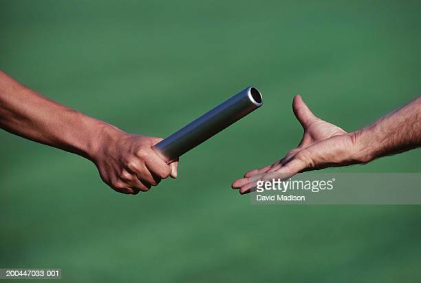 Baton change during relay race, close-up