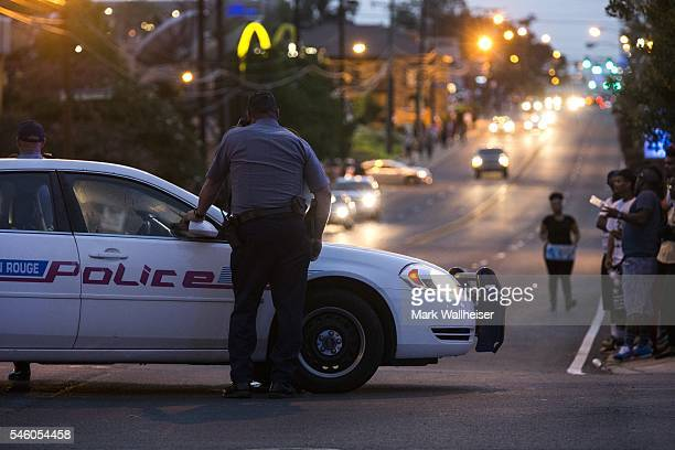 Baton Rouge police redirect traffic away from a protest march that resulted in scores of arrests after a march on July 10, 2016 in Baton Rouge,...