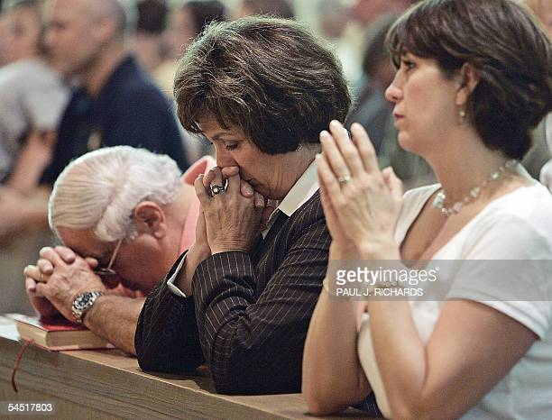 "Baton Rouge, UNITED STATES: Louisiana Governor Kathleen Blanco prays with her husband Raymond ""Coach"" Blanco and her daughter Karmen during services..."