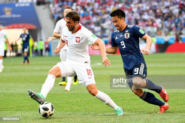 Batrosz Bereszynski of Poland and Shinji Okazaki of Japan fight for the ball during the 2018 FIFA World Cup Group H match between Japan and Poland at...