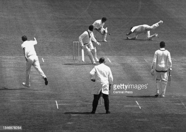 Batsman Garfield Sobers, captain of the West Indies cricket team and wicketkeeper Jim Parks look on as England slip fielder Colin Cowdrey dives in an...