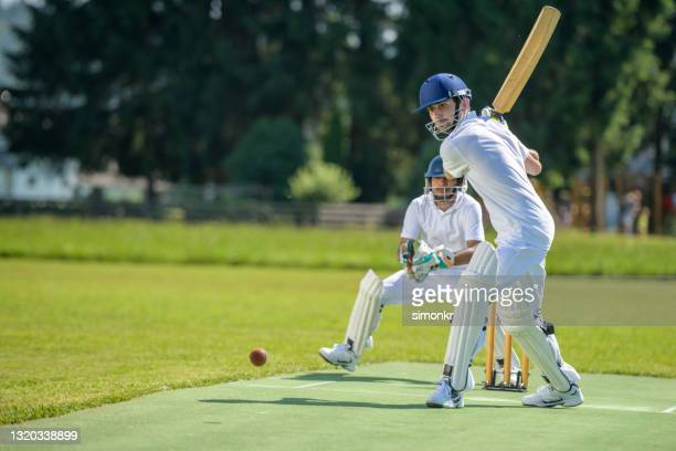 batsman hitting ball on pitch - cricket pitch stock pictures, royalty-free photos & images