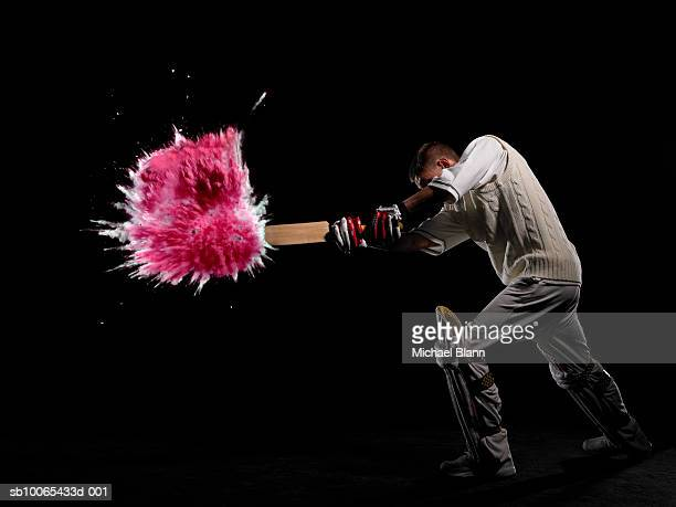 batsman hitting exploding powder ball, side view, studio shot - cricket player stock pictures, royalty-free photos & images
