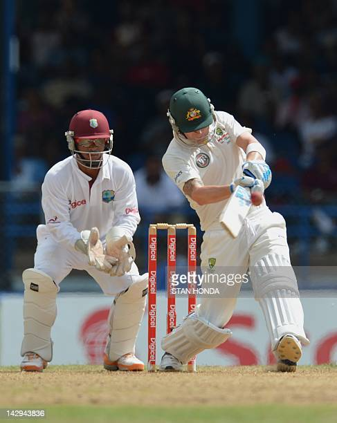 Batsman Michael Clarke of Australia hits a four as West Indies wicketkeeper Carlton Baugh watches during the first day of the secondofthree Test...