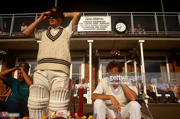 A batsman prepares to walk on to the field during a local club match in Paignton UK Adjusting his cap before taking to the field of play the young...