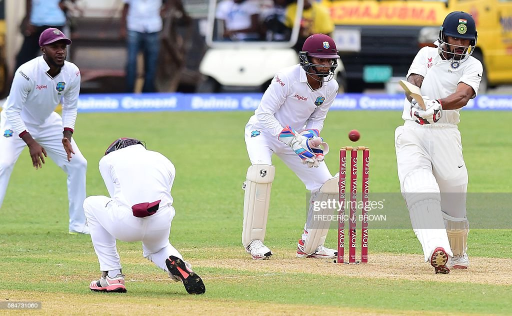 Batsman Shikhar Dhawan of India connects off a delivery from West Indies bowler Devendra Bishoo in the 18th over on July 30, 2016 in Kingston, Jamaica on the first day of the 2nd Test between India and the West Indies. / AFP / Frederic J. BROWN