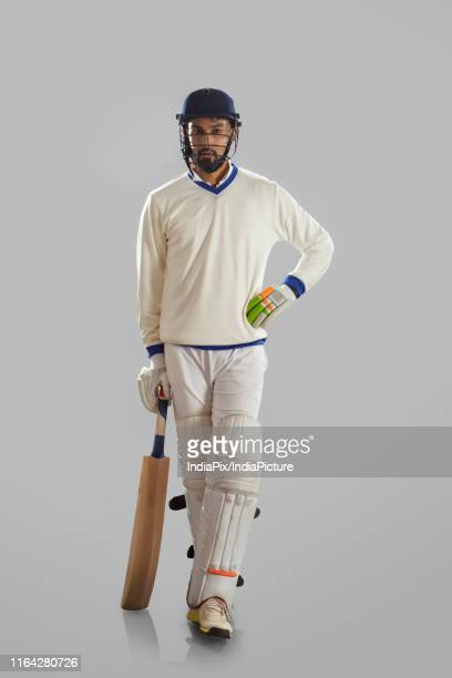 batsman standing on grey background - cricket player stock pictures, royalty-free photos & images