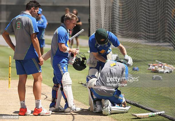 Batsmen David Warner and Mitchell Marsh attend to Joe Burns who slumps to the ground after being hit on the helmet by Scott Boland during an...