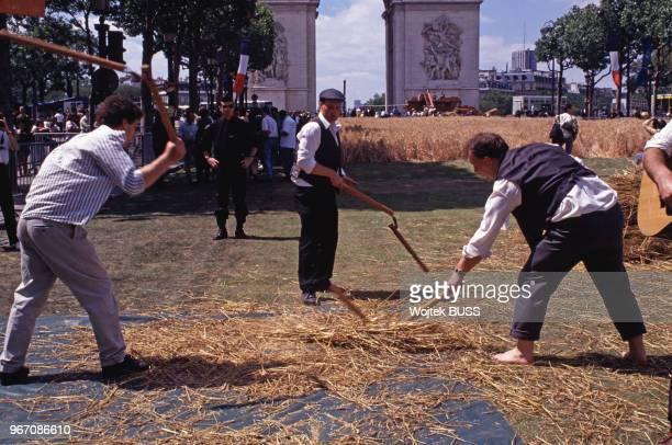 Battage du blé au fléau pendant la Grande Moisson sur les ChampsElysées à Paris le 24 juin 1990 France