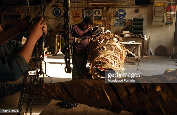 Battaglia artistic foundry in Milan This is the foundry where the works by Italian sculptor Arnaldo Pomodoro are made A worker refining a sculpture...