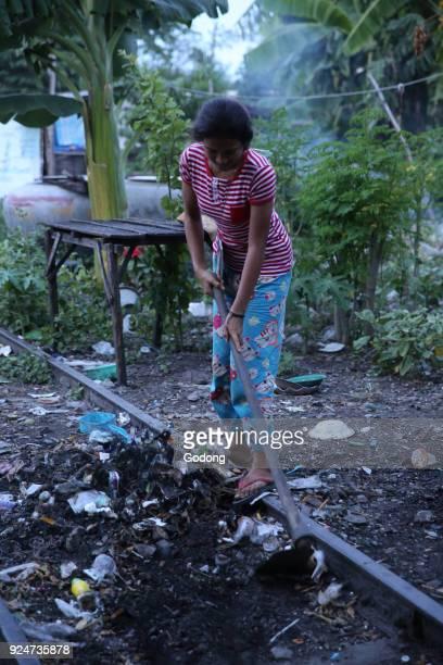 Battambang slum girl cleaning the ground outside her home Cambodia