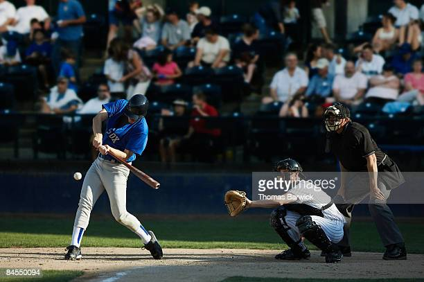 batter swinging at pitch, crowd in background - baseball pitcher photos et images de collection