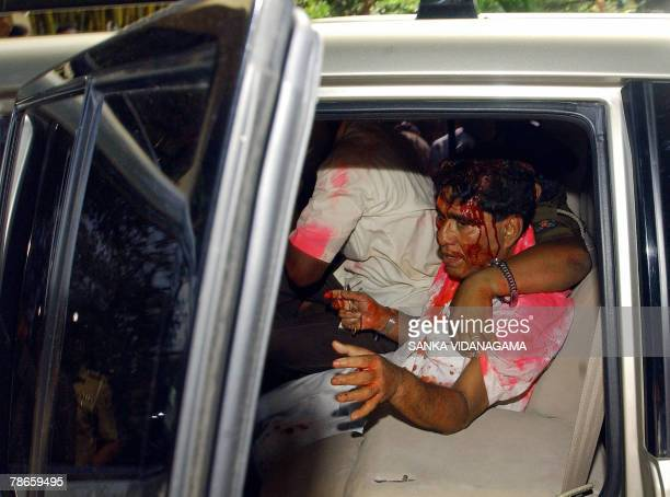 Battered and bruised Sri Lanka's Labour Minister Mervin Silva tries to close the door of his vehicle while a policeman puts his arm around him...