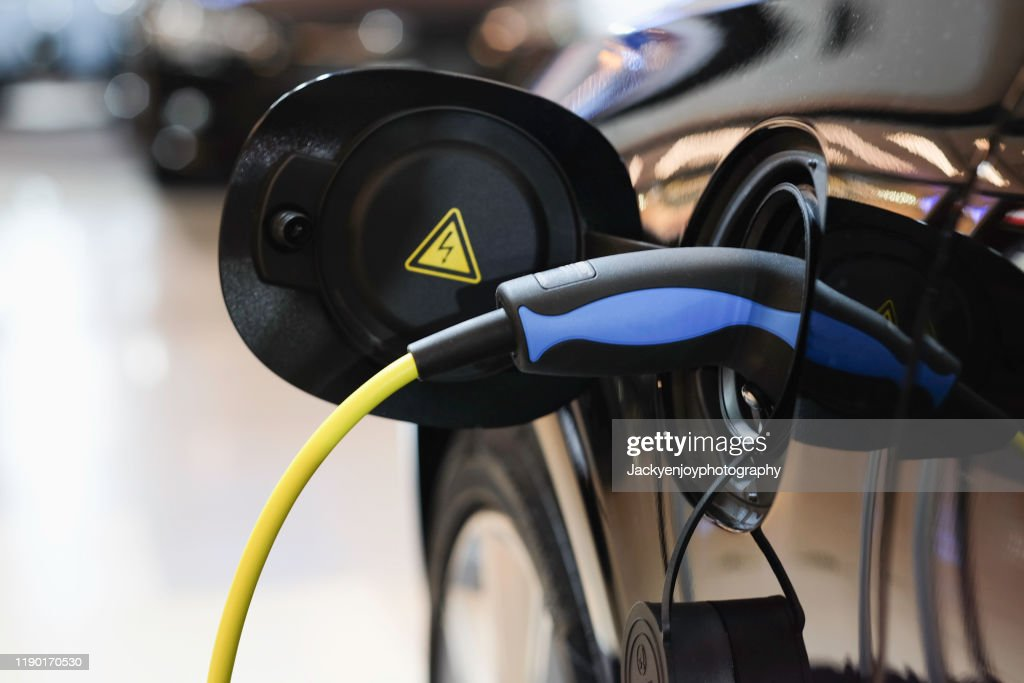 Battery charger in electric car at showroom : Stock Photo