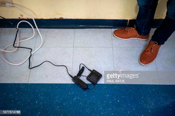 A battery for an ankle monitor is pictured charging on the floor of the church hall of the Basilica of San Albino in Mesilla New Mexico on January 3...