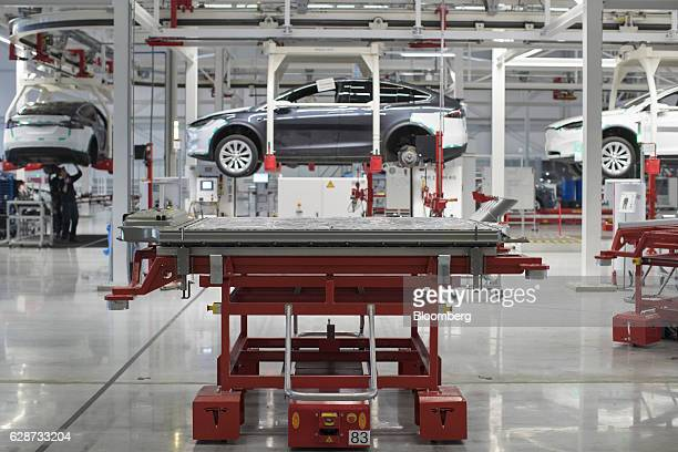 A battery pack stands on a trolley as Tesla Model X sports utility vehicles sit in cradles during assembly for the European market at the Tesla...