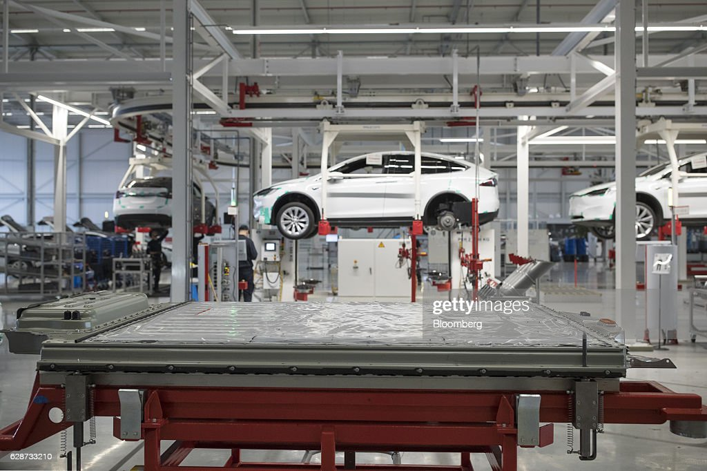 A battery pack stands on a trolley as Tesla Model X sports utility vehicles (SUV) sit in cradles during assembly for the European market at the Tesla Motors Inc. factory in Tilburg, Netherlands, on Friday, Dec. 9, 2016. A boom in electric vehicles made by the likes of Tesla could erode as much as 10 percent of global gasoline demand by 2035, according to the oil industry consultant Wood Mackenzie Ltd. Photographer: Jasper Juinen/Bloomberg via Getty Images